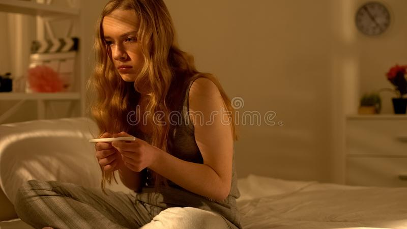 Anxious girl terrified with pregnancy test result, unwanted pregnancy, mistake. Stock photo stock photos