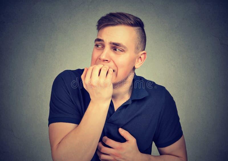 Anxious hesitant man biting his fingernails. Anxious hesitant young man biting his fingernails on gray background stock photos