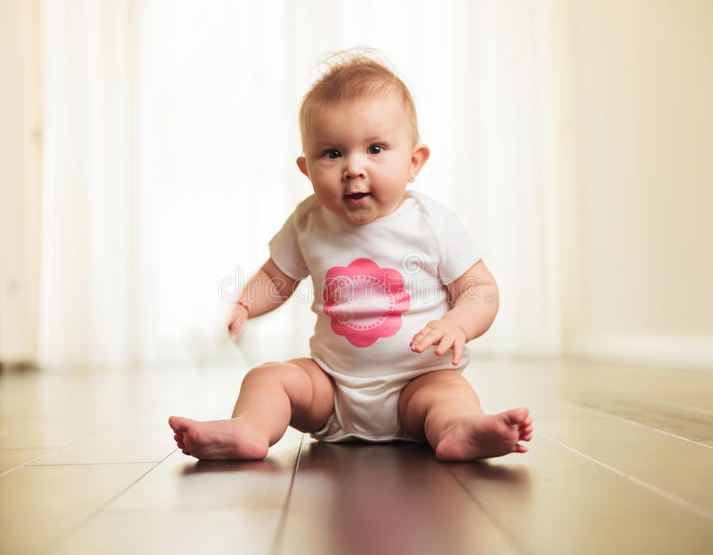 Anxious little baby girl sitting on wooden floor stock photography