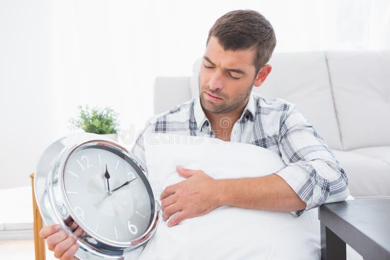 Anxious man beside a clock stock photography