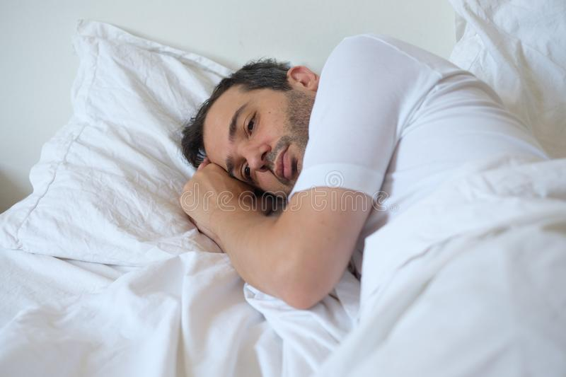 Anxious man lying in his bed and cannot sleep. Anxious man lying in his bed and feeling bad stock photos