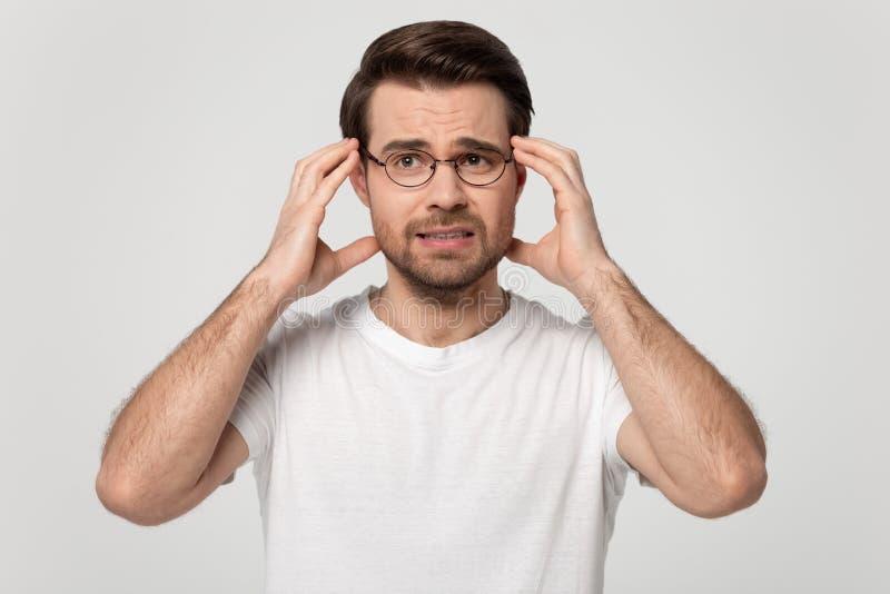 Guy touching head temples experiencing stress studio shot. Anxious millennial man wearing glasses white t-shirt touching head temples experiencing stress having stock image