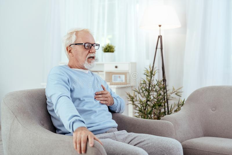 Anxious senior man suffering from heart discomfort. Old age. Alarmed senior man touching chest and posing in armchair stock photos