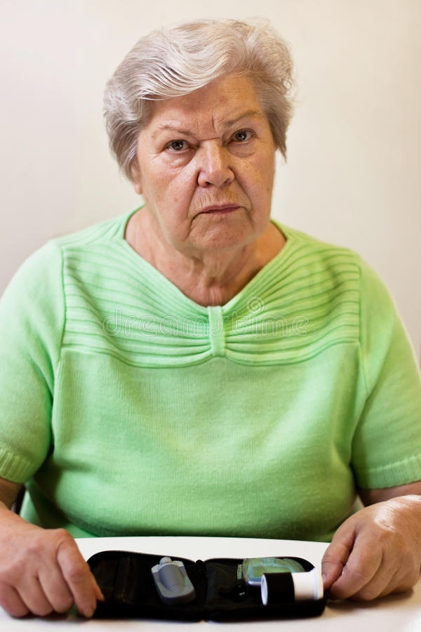 Anxious senior woman with blood sugar test. Old woman with equipment of blood sugar test stock photo