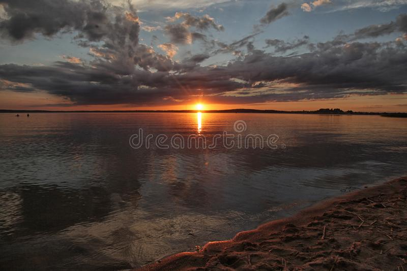 Anxious sunset. An alarming sunset on the lake sky and a reflection of a cloud royalty free stock image