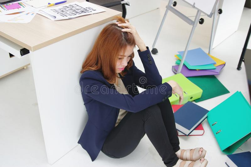 Anxious upset young Asian business woman with hands on head sitting on floor at her in workplace of office. stock photo