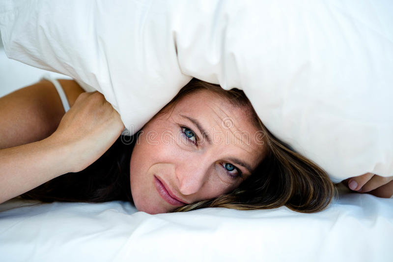 Anxious woman hiding under a pillow. Lying on her bed royalty free stock photos