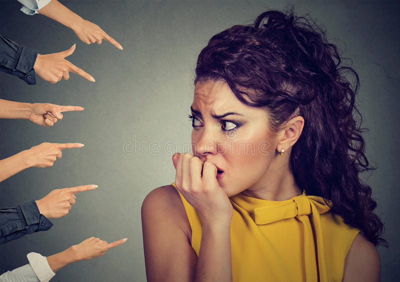 Anxious woman judged by different people fingers pointed at her. Concept of accusation of guilty girl. Negative human emotions face expression feeling stock photo