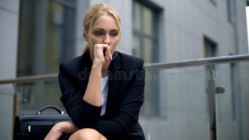 Anxious woman sitting on bench, worried about dismissal from work, depression. Stock photo stock images