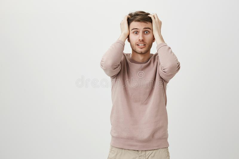 Anxious and worried young good-looking man holding hands on head, looking with popped eyes on something terrifying. Standing over gray background. Kitchen royalty free stock photography