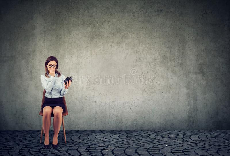 Anxious young woman with alarm clock waiting for an interview royalty free stock photo