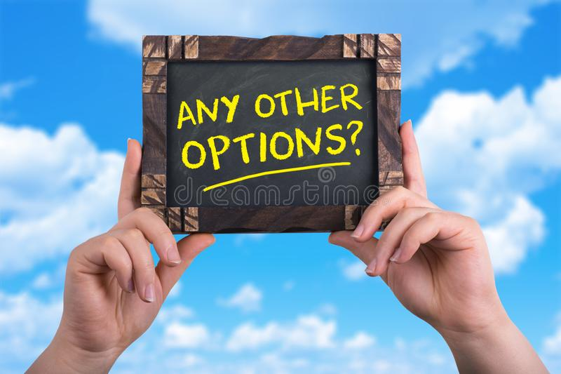Any other options. A woman holding chalkboard with words any other options on blue sky background royalty free stock photography