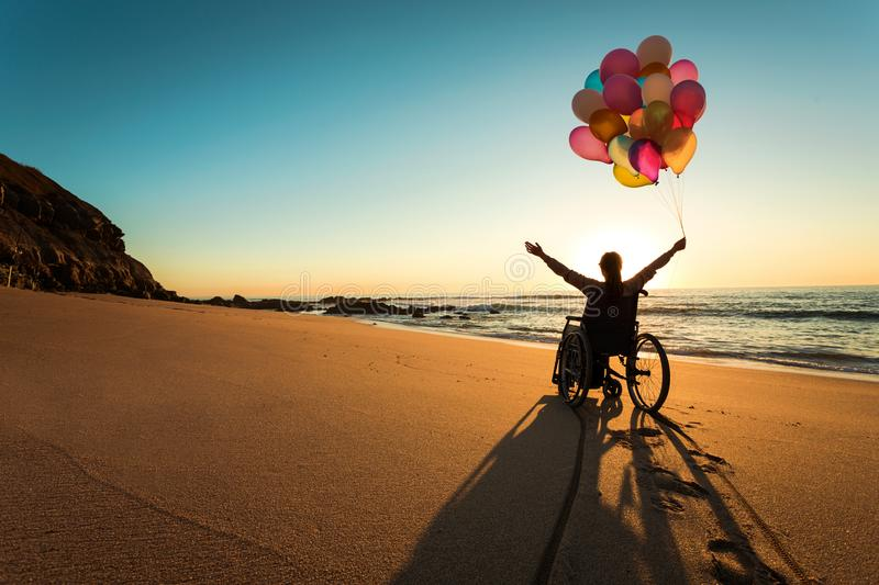 Anything is possible. Handicapped man on a wheelchair with colored balloons at the beach royalty free stock photos