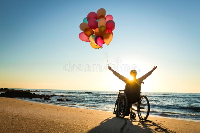 Anything is possible. Handicapped man on a wheelchair with colored balloons at the beach royalty free stock photo