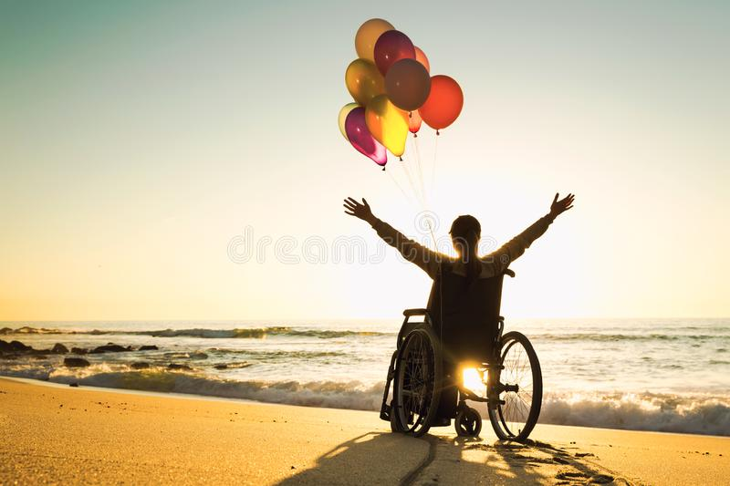 Anything is possible. Handicapped man on a wheelchair with colored balloons at the beach royalty free stock images
