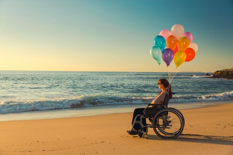 Anything is possible. Handicapped woman on a wheelchair with colored balloons at the beach royalty free stock photos
