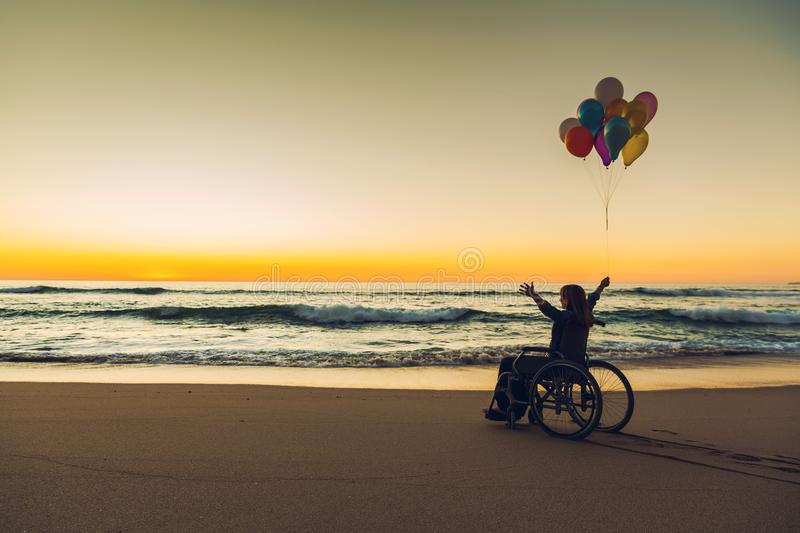 Anything is possible. Handicapped woman on a wheelchair with colored balloons at the beach stock photography