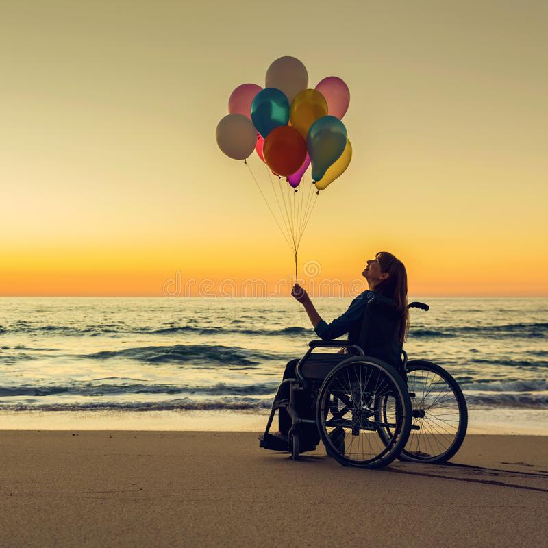 Anything is possible. Handicapped woman on a wheelchair with colored balloons at the beach royalty free stock photography