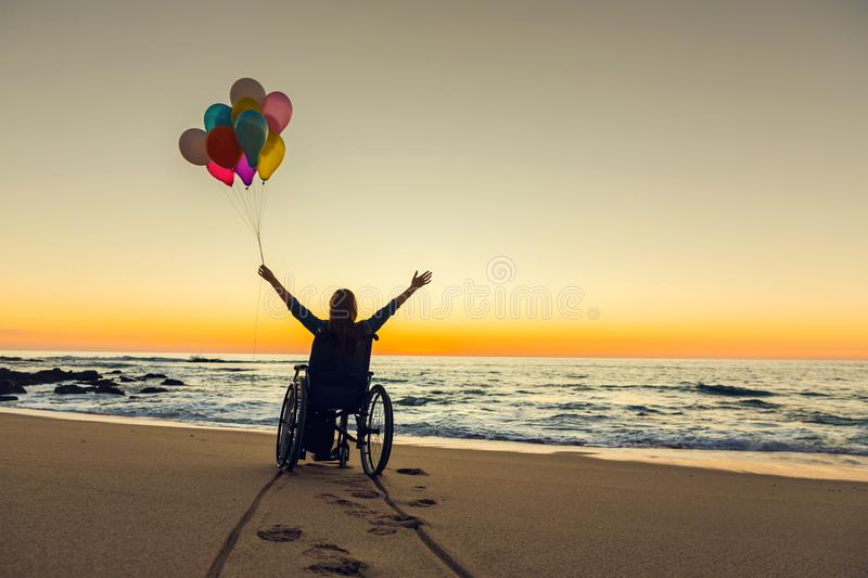 Anything is possible. Handicapped woman on a wheelchair with colored balloons at the beach royalty free stock images