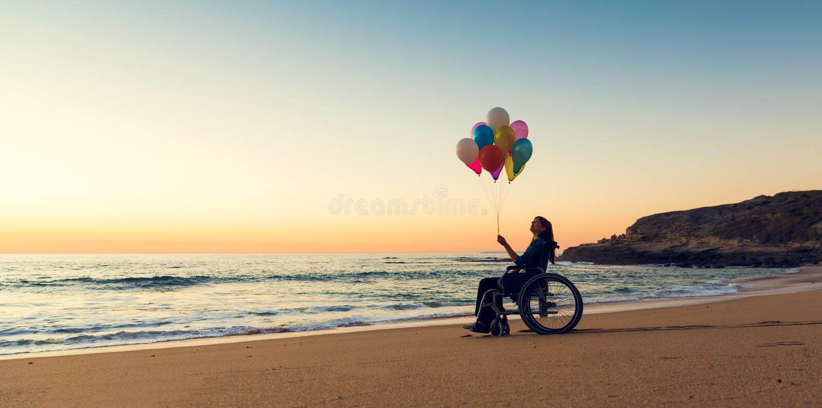 Anything is possible. Handicapped woman on a wheelchair with colored balloons at the beach stock photo