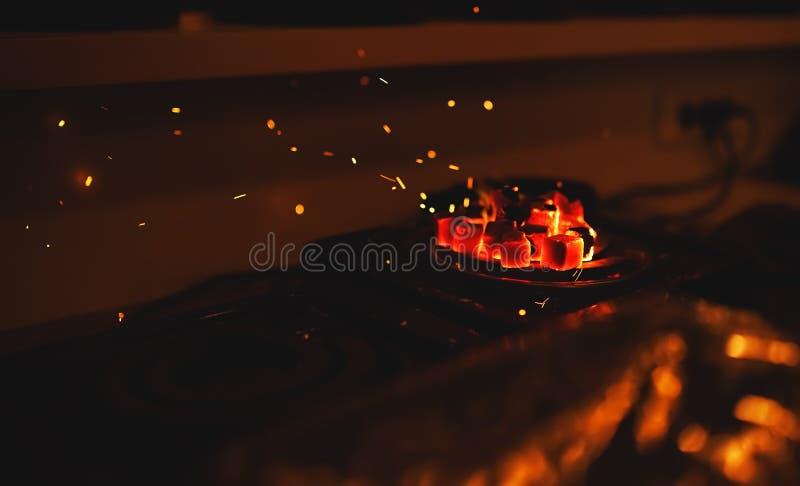 Anzünden der quadratischen Kohle für eine Huka auf einem speziellen Ofen mit einer heißen Spirale stockfotografie