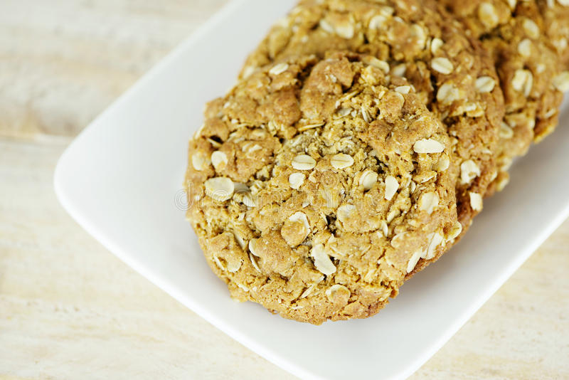 Anzac Biscuits. Pile of freshly baked Anzac biscuits on a white plate; these sweet homemade Australian and New Zealand oats and coconuts biscuits are stock photography