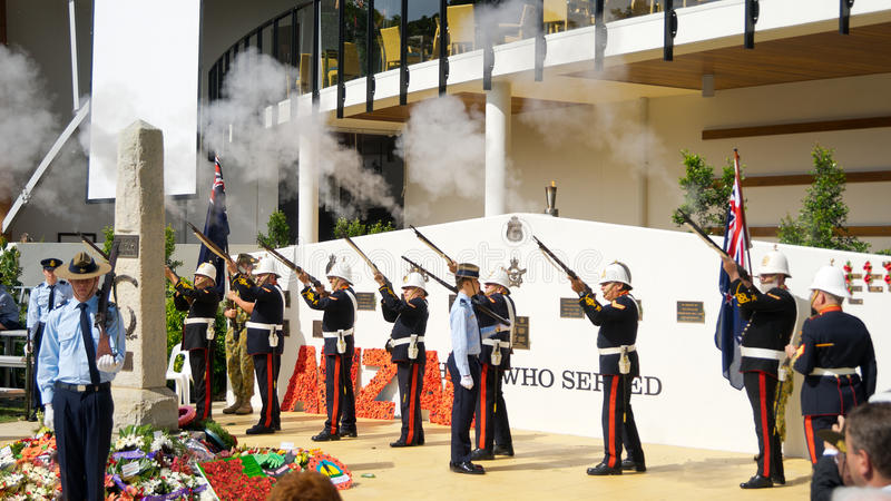 Anzac Day Rifle Salute. A group of veteran military soldiers dressed in formal uniform on executing a rifle salute during the commemoration of Anzac Day in stock image