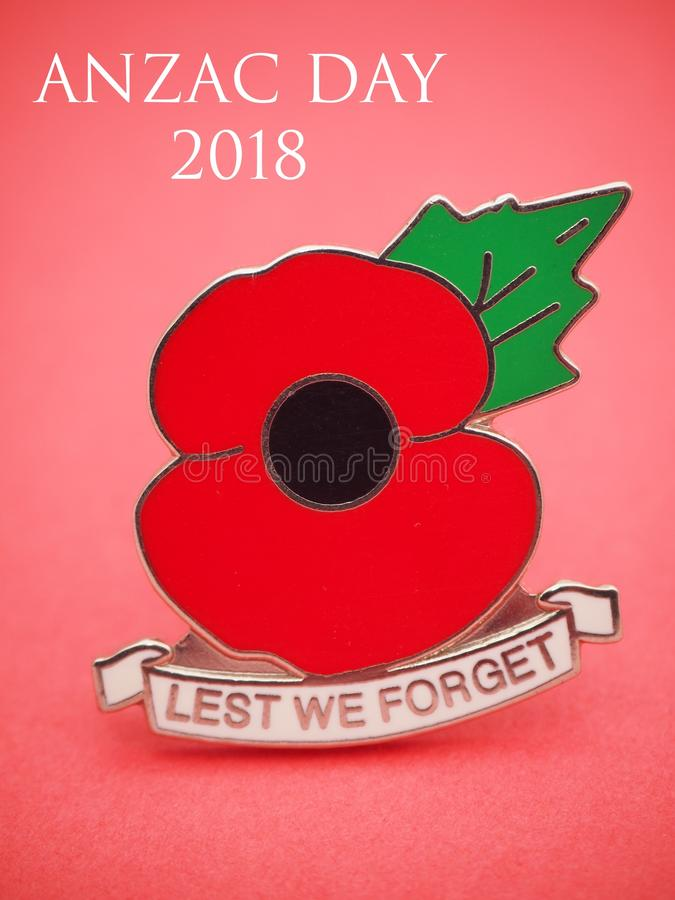 ANZAC Day 2018. With text on light red background with focus fade on , with large picture of the universal generic medal badge of poppy with LEST WE FORGET stock image