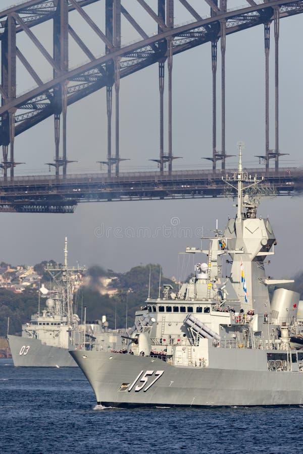 Anzac-grupp f?r HMAS Perth FFH 157 fregatt av seglingen f?r kunglig australisk marin under den iconic Sydney Harbor Bridge fotografering för bildbyråer