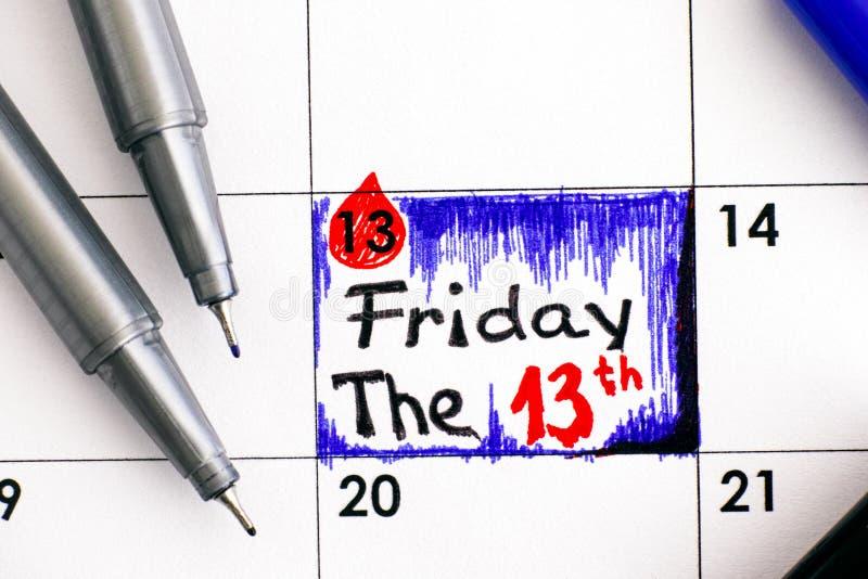 Anzeige Freitag das 13. im Kalender mit Stiften stockfotografie