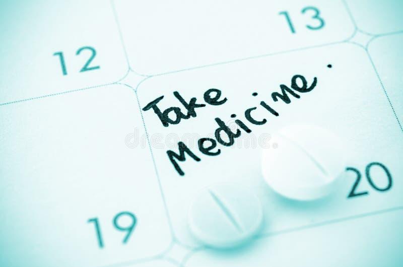 Anzeige nehmen Medizin auf Kalender ein lizenzfreie stockfotografie