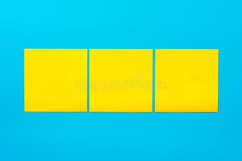 Anzeigen- und Kombinationskonzept Abschluss herauf drei gelbe leere quadratische Aufkleber auf blauem Hintergrund mit Kopie spase stockfoto