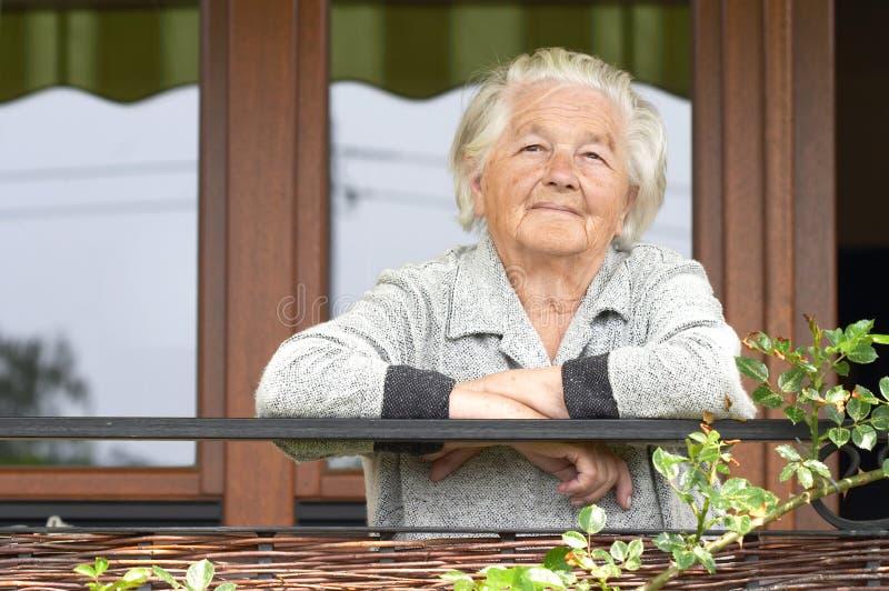 Anziana sul portico fotografia stock libera da diritti