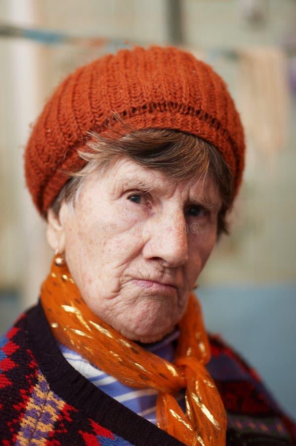 Anziana triste in berreto rosso fotografia stock libera da diritti
