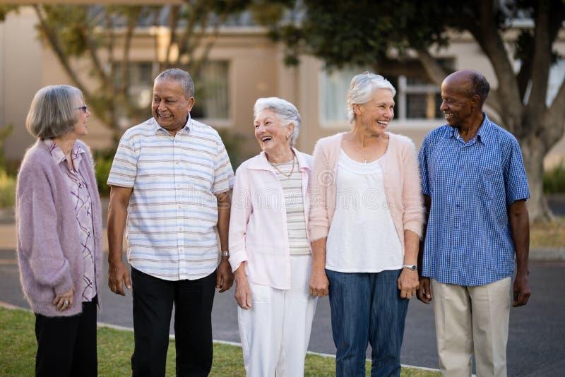 Anziani allegri che stanno mentre esaminandose immagini stock libere da diritti
