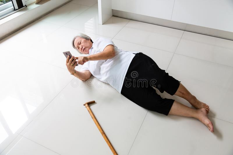 Anziani asiatici con il bastone da passeggio e per mezzo del telefono richiedere aiuto, donna senior malata con l'emicrania, mal  fotografie stock