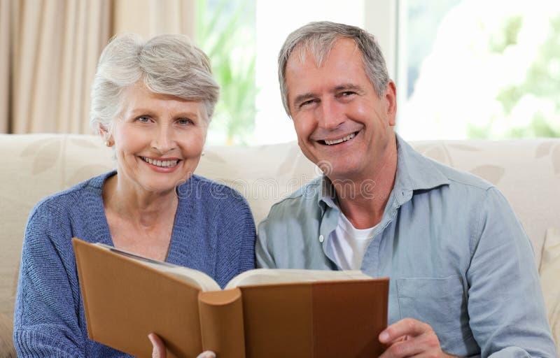 Anziani che esaminano il loro album di foto immagine stock libera da diritti