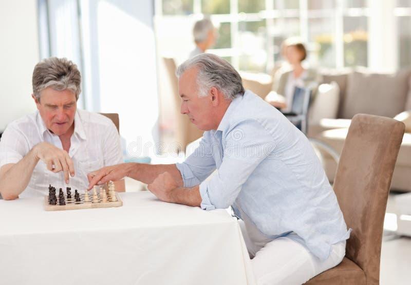 Anziani che giocano scacchi nel salone fotografia stock libera da diritti
