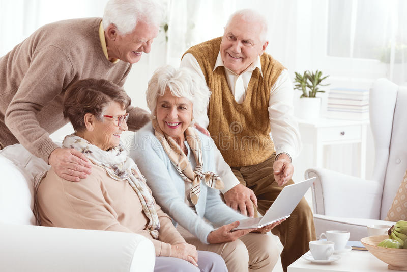Anziani che godono della tecnologia moderna fotografia stock