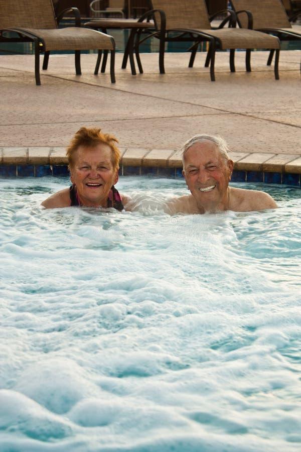 Anziani che godono della vasca calda fotografie stock