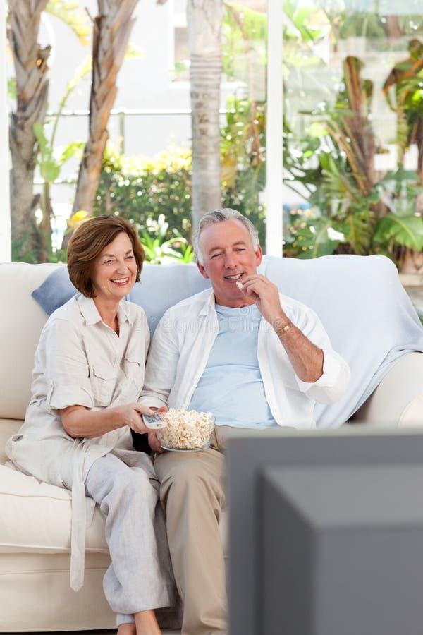 Anziani che guardano TV nel paese immagini stock