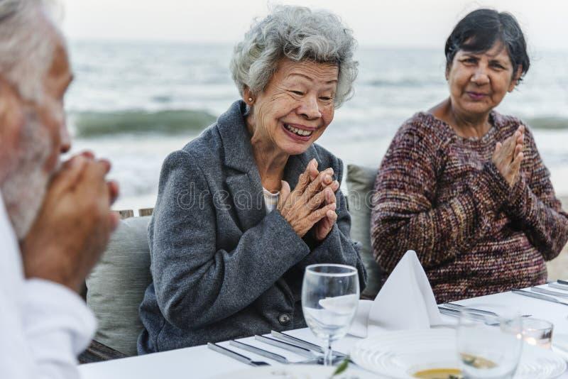 Anziani che hanno un partito di cena alla spiaggia immagine stock