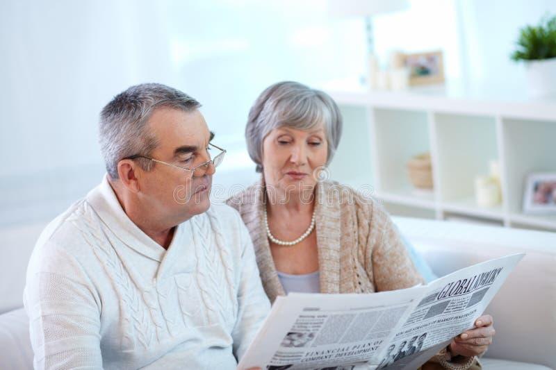 Anziani che leggono carta fotografie stock