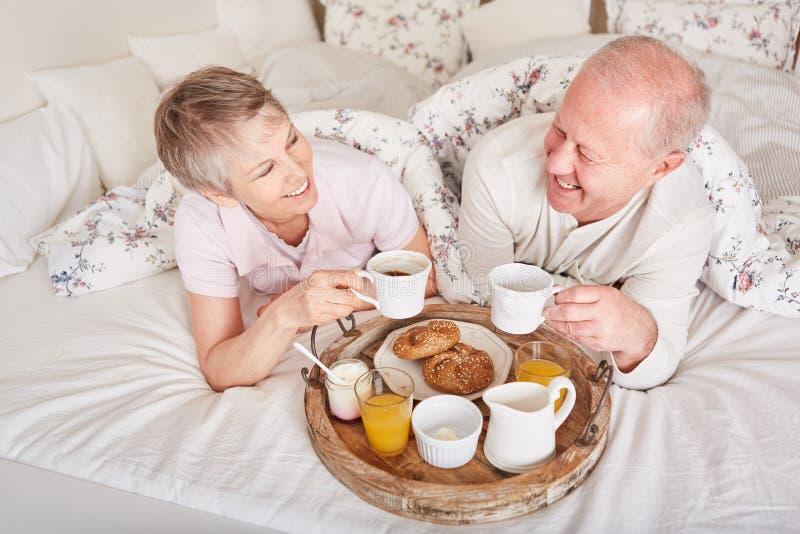 Anziani che mangiano prima colazione nella camera di albergo fotografie stock