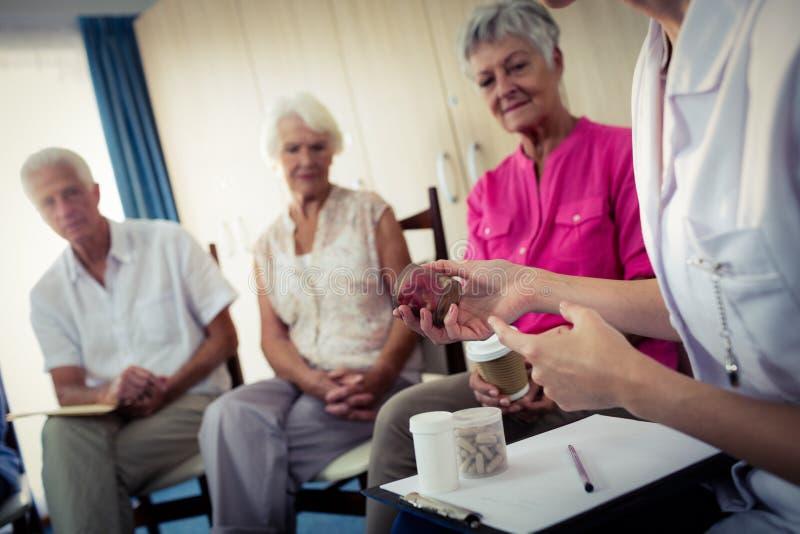Anziani che parlano con l'infermiere circa il farmaco immagini stock libere da diritti