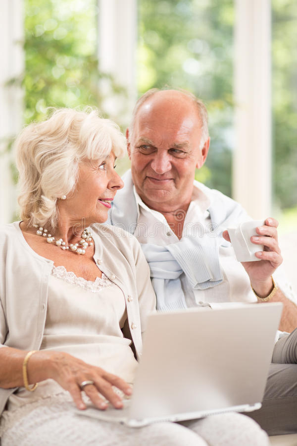 Anziani che per mezzo del computer portatile per comunicare immagine stock