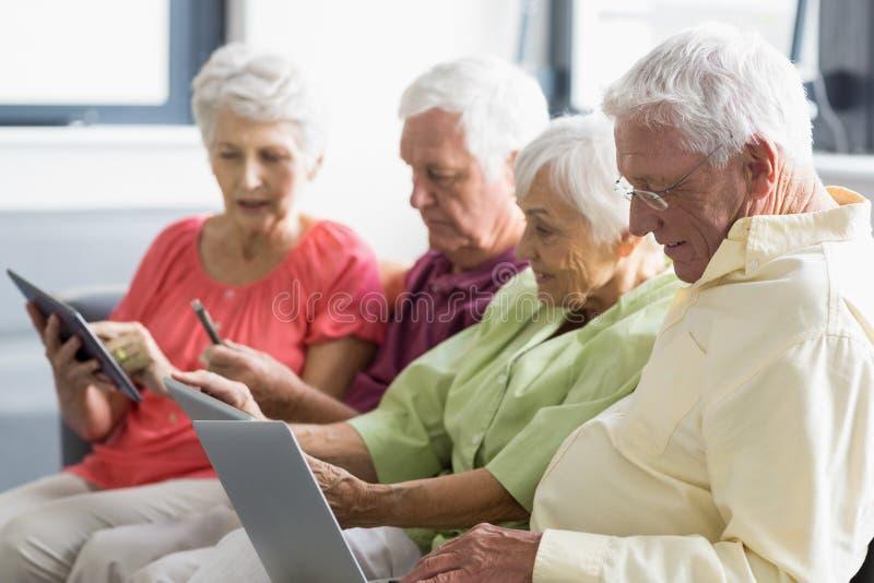 Anziani che per mezzo delle compresse fotografie stock