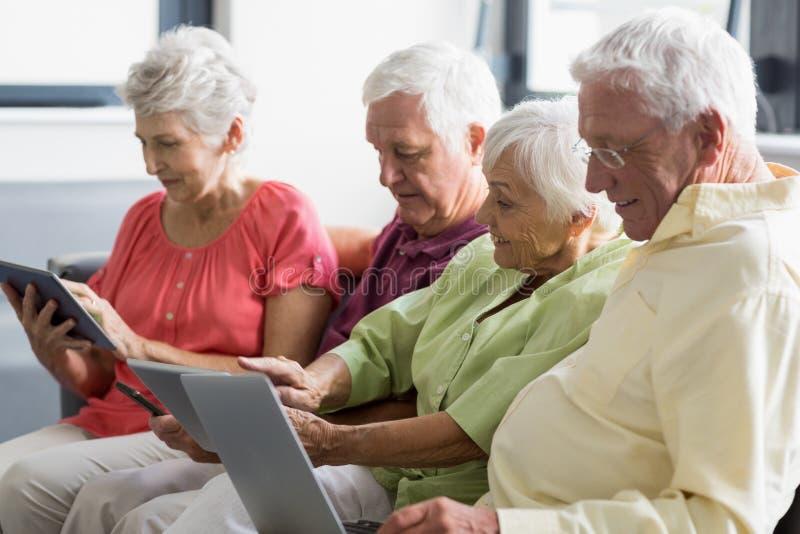 Anziani che per mezzo delle compresse fotografia stock
