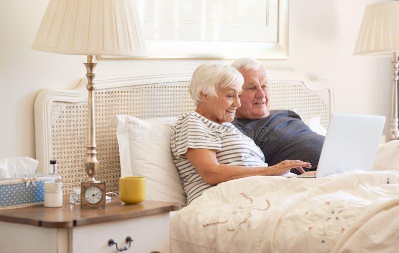 Anziani che per mezzo di un computer portatile sul loro letto di mattina fotografia stock libera da diritti