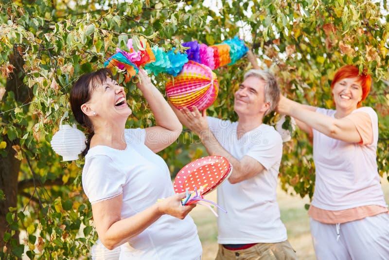 Anziani che ridono e che si divertono mentre decorando per un partito fotografia stock libera da diritti